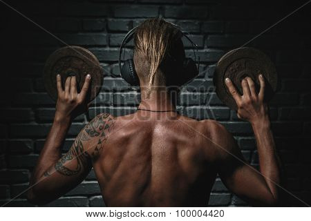 Muscular young man lifting weights and listening to music in headphones