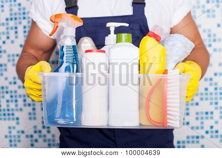 Cheerful young cleaner is presenting his equipment
