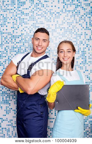 Cheerful young workers are doing clean-up in bathroom