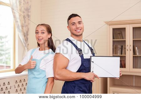 Attractive young workers in apron are cleaning the house