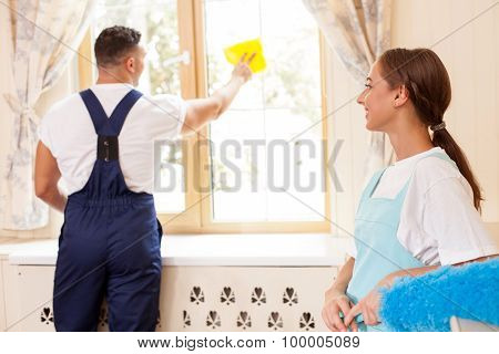 Cheerful young cleaners are cleaning a house together