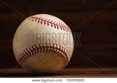 A white leather baseball on a wooden bench background