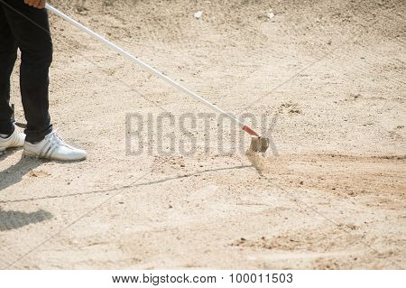Golfer Racking Sand At Golf Course, Thailand