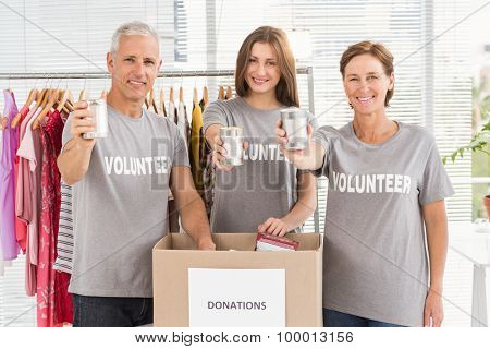 Portrait of smiling volunteers showing donated cans in the office