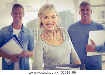Portrait of smiling business colleagues holding workbooks at office