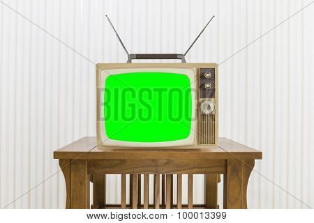 Old television with antenna on wood table with chroma screen.