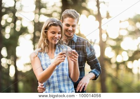 Happy smiling couple looking at pictures in the nature