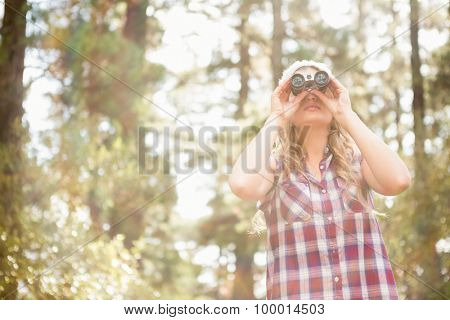 Pretty young blonde looking through binoculars in the nature