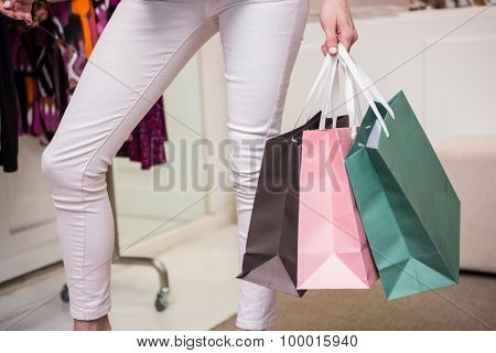 Woman standing with shopping bags in fashion boutique