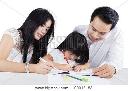 Child Write On The Book With Her Parents
