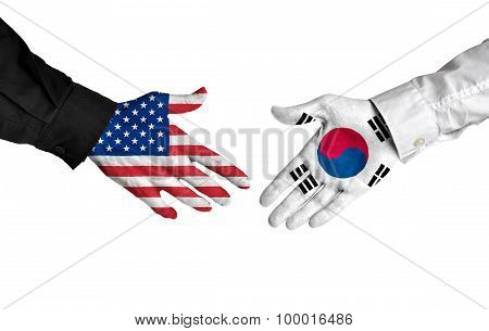 United States and South Korea leaders shaking hands on a deal agreement