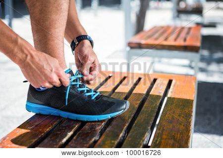 Side view of an athletic man tying his shoelaces on the bench