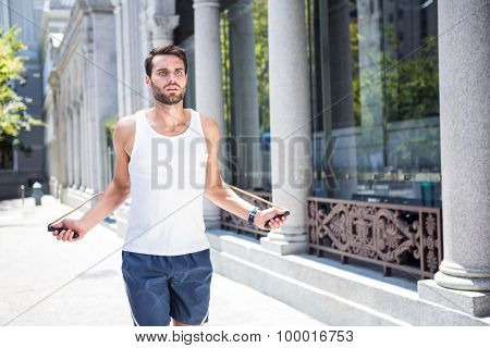 Handsome athlete skipping with jump rope in the city