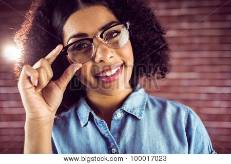 Portrait of smiling attractive hipster posing with glasses against red brick background