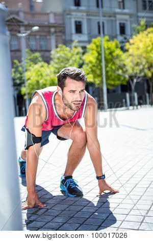 Side view of an handsome athlete in running stance on a sunny day