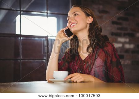 Smiling brunette having coffee and phoning at coffee shop