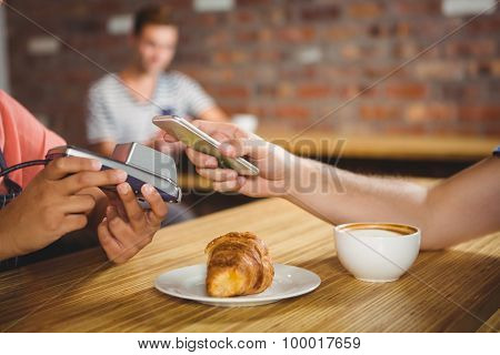 Paying for a croissant and a coffee with his smartphone at a cafe