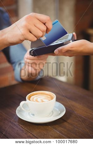 Male customer paying with credit card at coffee shop