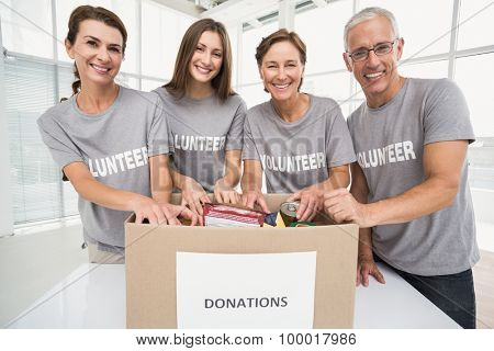 Portrait of smiling volunteers sorting donation box in the office