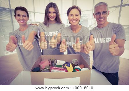 Portrait of smiling volunteers doing thumbs up in the office