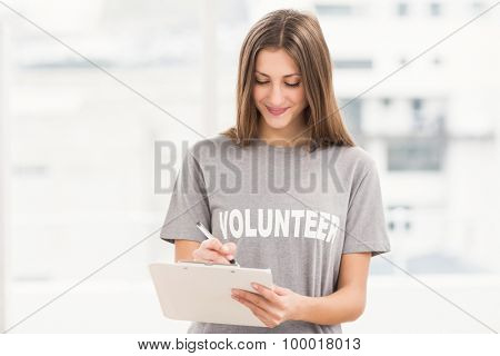 Smiling brunette volunteer writing on clipboard in the office