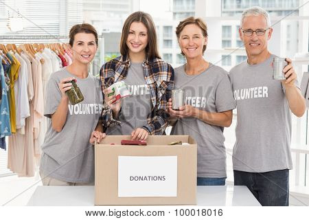 Portrait of smiling volunteers showing donations in the office