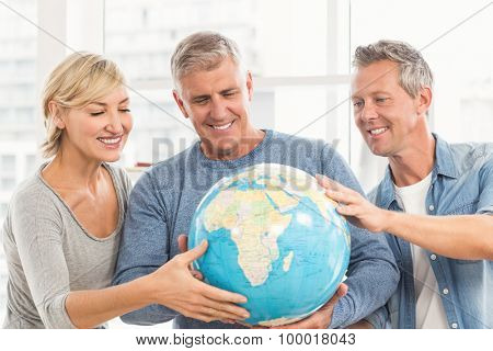 Happy business colleagues holding terrestrial globe at office