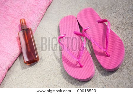 Travel Concept - Pink Flip Flops And Suntan Lotion Bottle On Sandy Beach