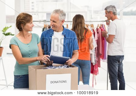 Smiling casual business colleagues with donation box in the office