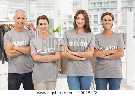 Portrait of smiling volunteers with arms crossed in the office
