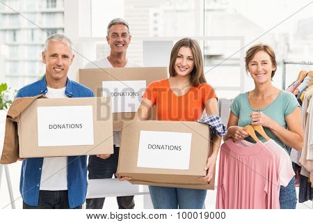 Portrait of smiling casual business people with donation boxes in the office