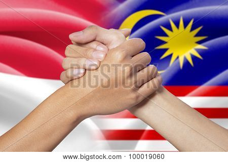Partnership Hands With Indonesian And Malaysian Flags