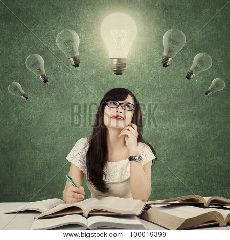 Smart Learner Sitting Under Light Bulb