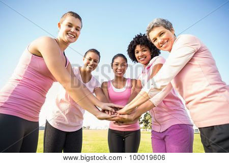 Women wearing pink for breast cancer and putting hands together in parkland