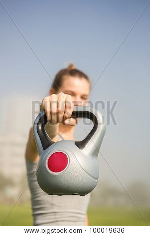 Sporty blonde lifting kettlebell in parkland