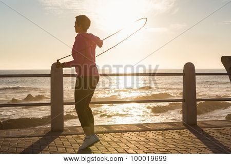 Sporty woman skipping at promenade on a sunny day
