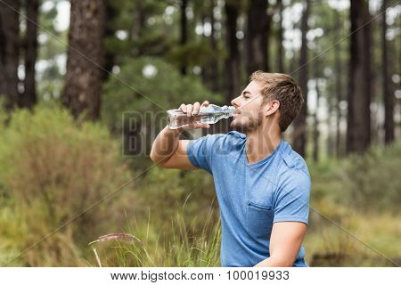 Young handsome man drinking water in the nature