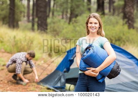 Portrait of a young pretty hiker holding a sleeping bag in the nature
