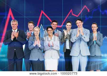 Smiling business team applauding at camera against stocks and shares