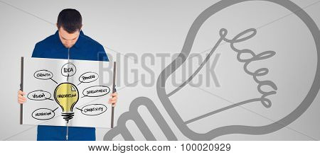 Manual worker showing a book against grey vignette