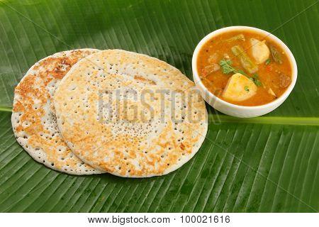 Dosa and sambar served on banana leaf.