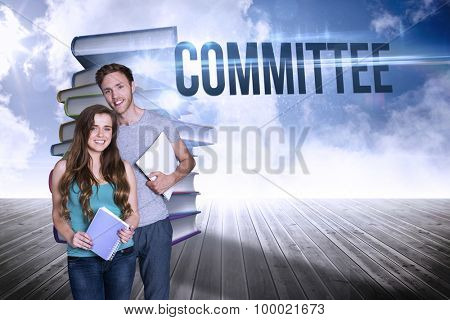 The word committee and portrait of smiling young couple with books against stack of books against sky