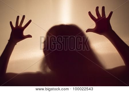 female scary silhouette behind a fabric wall