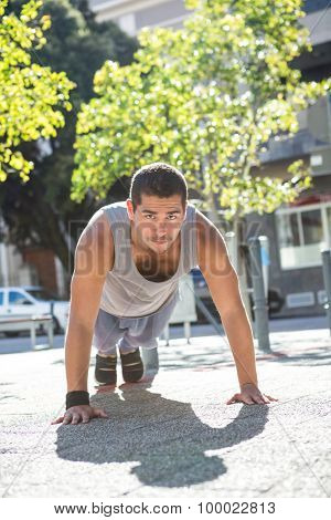 A muscular man on plank position on a sunny day