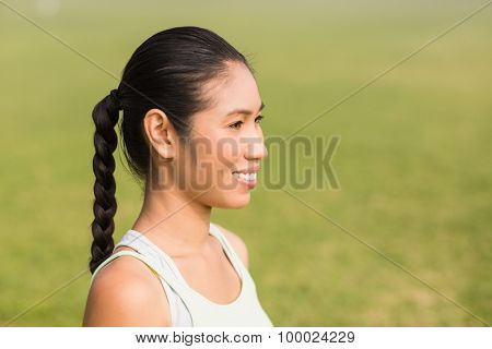 Smiling sporty woman looking away in parkland