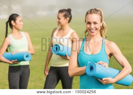 Portrait of smiling sporty blonde in front of friends in parkland
