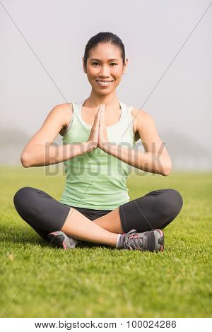 Portrait of smiling sporty woman doing yoga in parkland