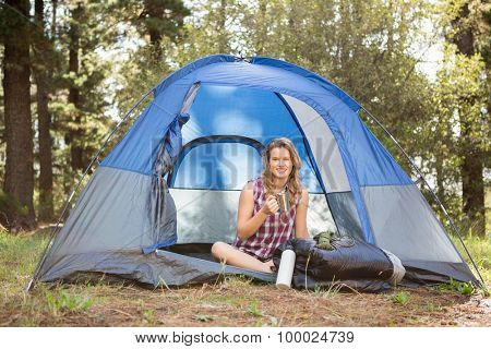 Portrait of pretty blonde camper smiling and sitting in tent in the nature