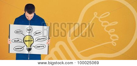 Manual worker showing a book against orange background