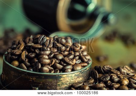 Roasted coffee beans spilled freely on a wooden table. Coffee beans in a dish